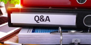 Stack of big binders with one labeled Q&A for Questions and Answers