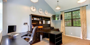 Home office with desk, credenza, and several clocks set to various timezones