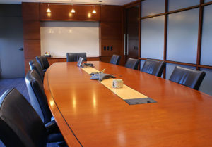 Long wooden conference table surounded by leather chairs